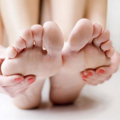 Отрывает пальцами отсохшую мозоль на ноге